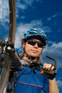 portrait of a young bicyclist in helmet with bicycle